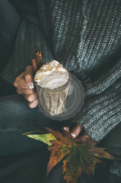Woman in grey woolen sweater holding mug with hot chocolate