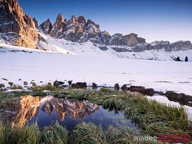 Mountain range reflected in lake at sunset with snow Dolomites Italy