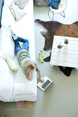 Woman relaxing on couch using laptop