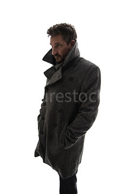 A semi-silhouette of a mystery man in a big coat, looking around – shot from eye level.