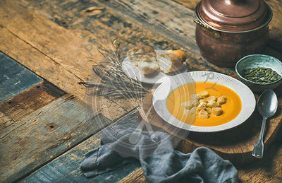 Fall warming pumpkin cream soup with croutons and seeds on board over rustic wooden background