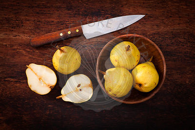yellow pears in wooden bowl on wooden table