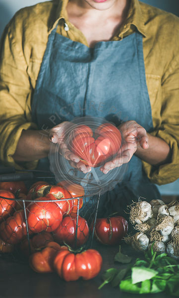 Woman in linen apron holding ripe heirloom tomato for cooking