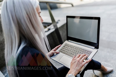 Young businesswoman sitting on stairs in the city using laptop
