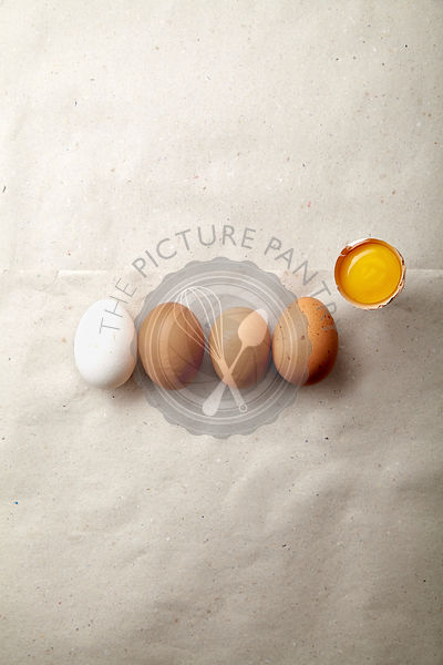 Four eggs of different natural tint with one egg yolk