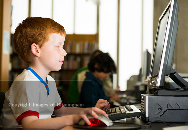 Child in The New Art Gallery Walsall library, working on a computer