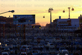 Traffic congestion on Av Juan Pablo II near ex-tranca Rio Seco at sunset, Blue Line cable cars in background, El Alto, Bolivia