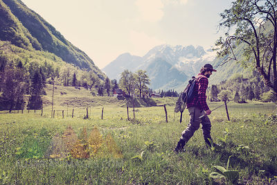 Slovenia, Bovec, angler walking on meadow towards Soca river