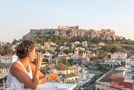 Woman drinking in front of the Acropolis at sunset. Athens, Greece