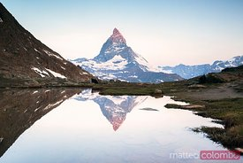 First light on the summit of Matterhorn reflected in Riffelsee