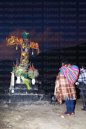 Quechua lady praying at the last cross on the pilgrimage trail after sunset, Qoyllur Riti festival, Peru