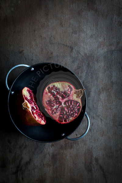 Pomegranate cut in halves in black bowl on wooden tabletop. Top view