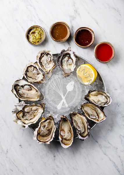Open Oysters with lemon and sauce on white marble background
