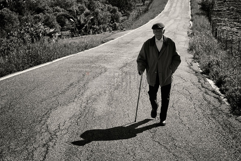 Elderly Man Walking down a Country Road