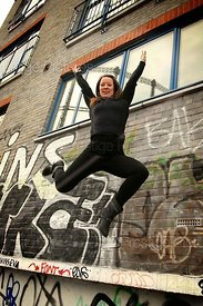 Woman Leaps in Front of Graffiti Wall in Theatrical Style
