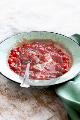 Strawberry Basil Jam served in a enamel bowl. Photographed on a rustic white background.