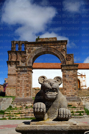 Puma statue in plaza in front of entrance archway and Nuestra Señora de la Asunción church, Juli, Puno Region, Peru