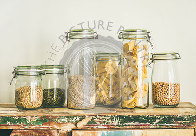 Various uncooked cereals, grains, beans and pasta for healthy cooking in glass jars on rustic table