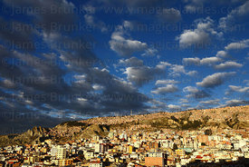 Dramatic clouds over houses on hillside on suburb of La Paz looking towards Ciudad Satelite in El Alto, Bolivia
