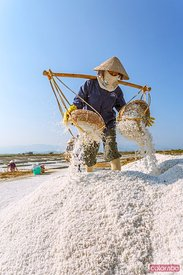 Vietnamese woman working in the salt pans, Vietnam