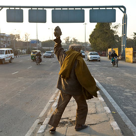 A homeless mentally ill man throws rocks at passing traffic,  Delhi, India