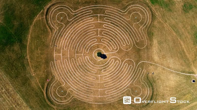 Aerial view zooming in of Willen Lake Maze, Milton Keynes filmed by drone in summer, United Kingdom