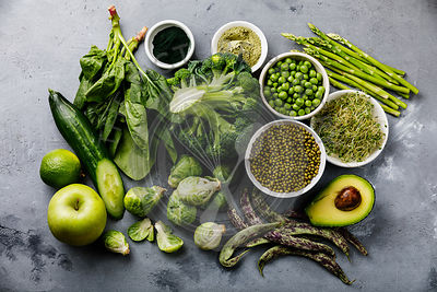 Healthy Green food Clean eating selection Protein source for vegetarians: asparagus, avocado, broccoli, spinach, spirulina, green peas on gray concrete background