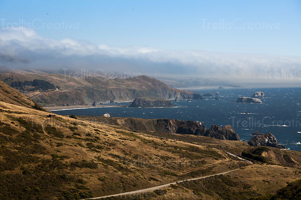 Fog lifts over the hills of the Great Highway along the Northern California coast.