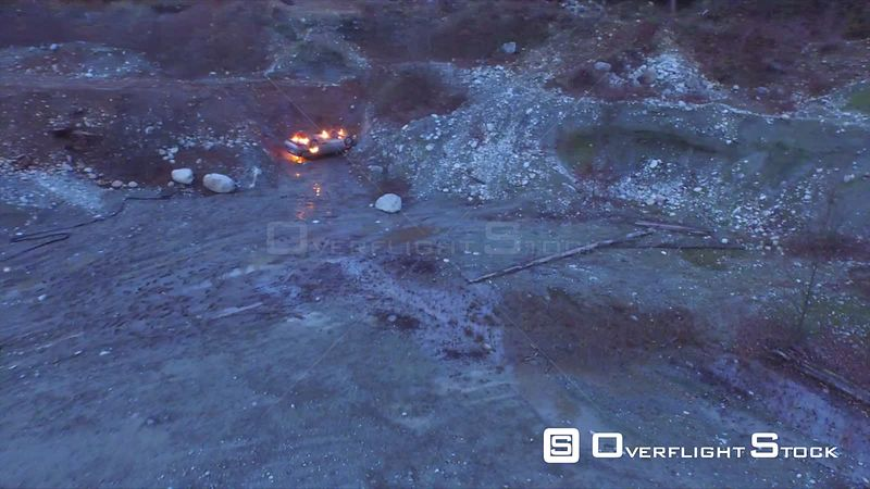 Car Fire on Turned Over Vehicle at Dusk in an Abandoned Gravel Pit.