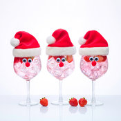 Glass of Gin with Santa hat on white background