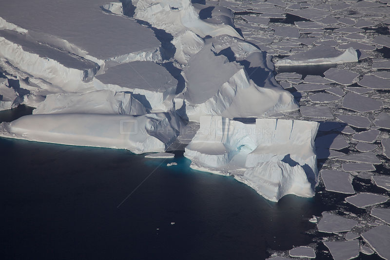 Aerial view of caved icebergs holding pack ice, Antarctica, March 2011.