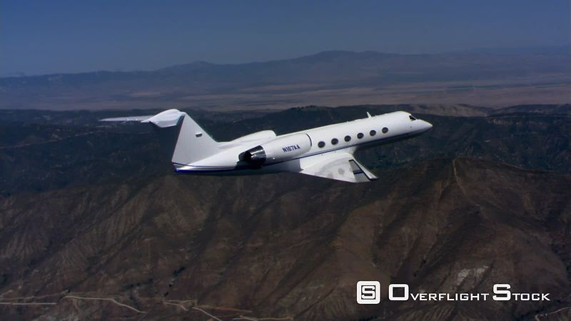 Air-to-air side view of business jet over barren hills