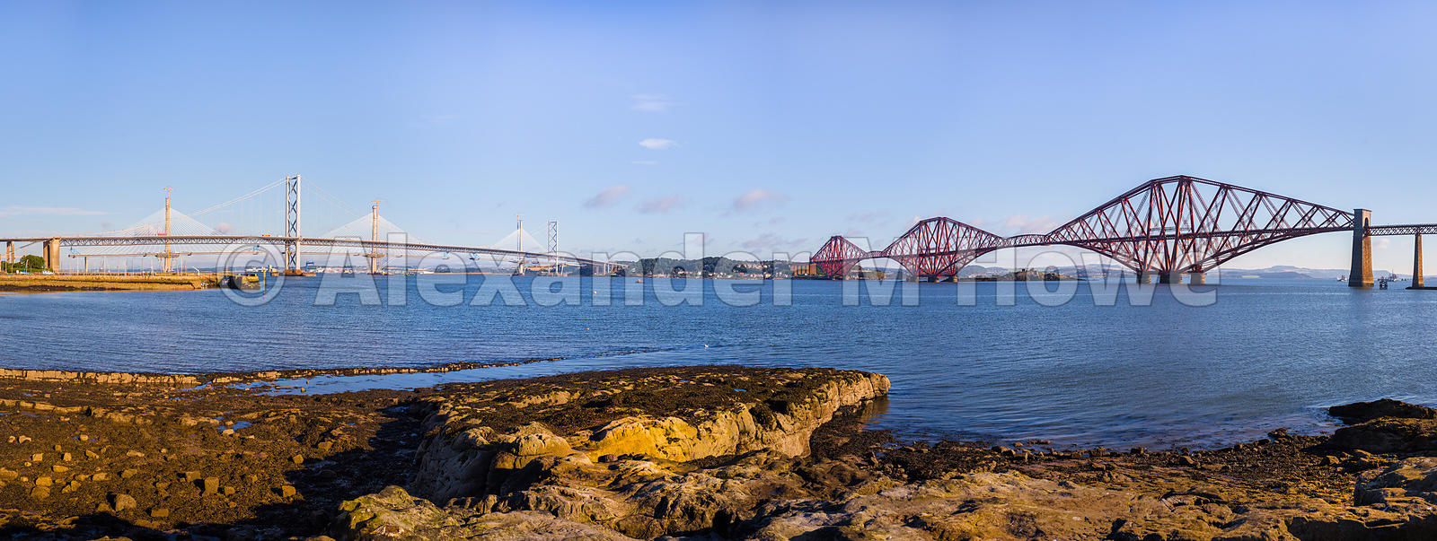The Forth Bridge and the Forth Road Bridge against a blue sky