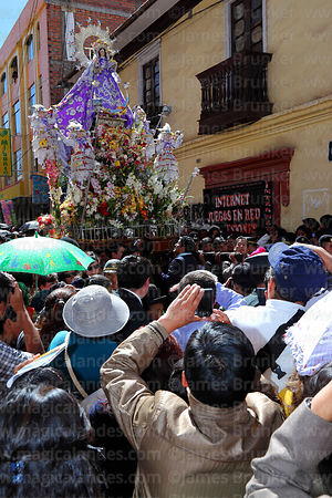 Main taking photo of Virgen de la Candelaria during main procession through the streets of Puno , Peru