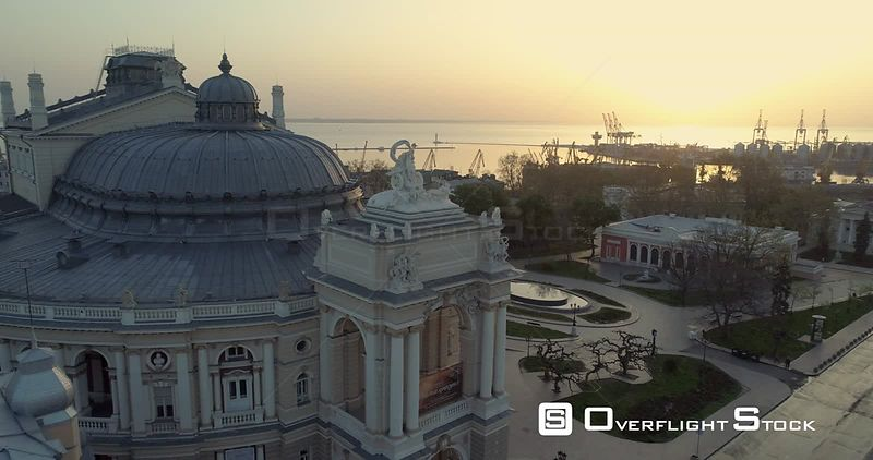 Aerial camera slowly descends the Odessa Opera Theatre with port in the background. The sun is rising over Black Sea behind Ukraine