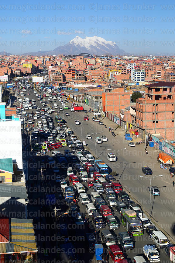 Traffic congestion on Av Juan Pablo II near ex-tranca Rio Seco, Mt Illimani in background, El Alto, Bolivia