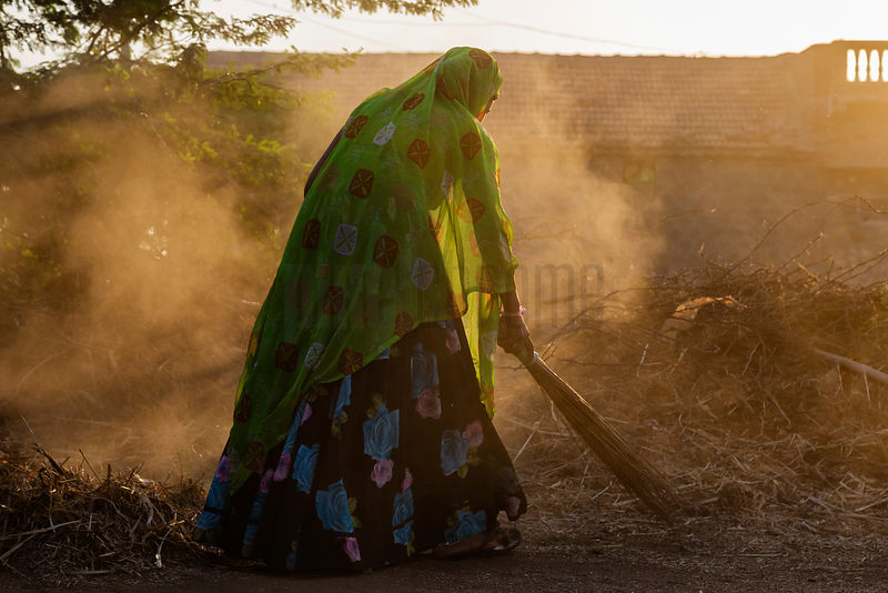 Woman Sweeping Outside her Home.
