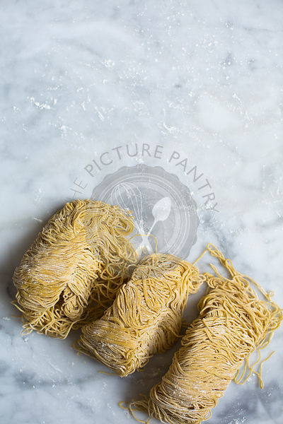 Fresh egg noodles and flour on marble background