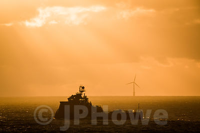 Ship and Wind Turbine in Silhouette against an Orange Sky