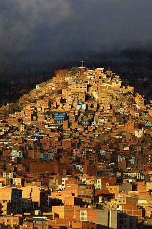 Storm clouds over brick houses on hillside on suburb of La Paz during rainy season , Bolivia