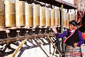 Local tibetan woman spinning prayer wheels, Tibet