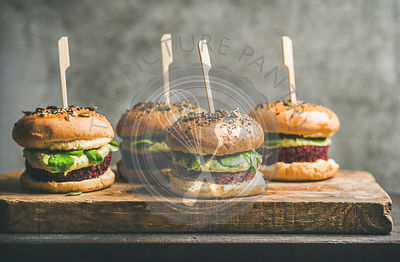 Vegan burgers with beetroot patties and green sprouts on board