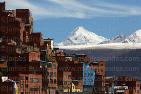 Houses on steep hillside in suburbs and Mt Huayna Potosí after fresh winter snowfall, La Paz, Bolivia