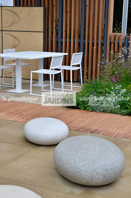 Terrasse contemporaine, mobilier de jardin : table et chaise collection Japan (Fabricant Estudi Hac), Sculpture en forme de galets (Sculpteur : Ben Barrell), Paysagiste : Robert Myers, CFS, Angleterre