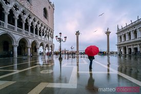 Woman with red umbrella in St Mark's square at high tide, Venice