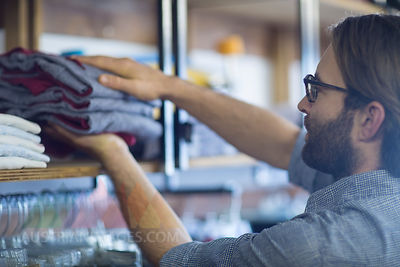 Salesperson putting putting clothes in store
