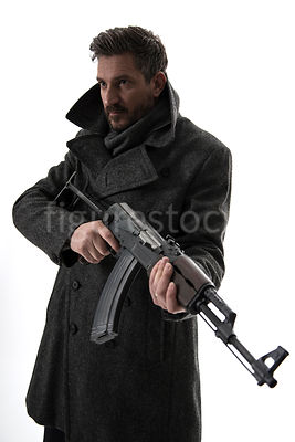 A silhouette of a mystery man in a big coat, holding an AK-47 – shot from eye level.