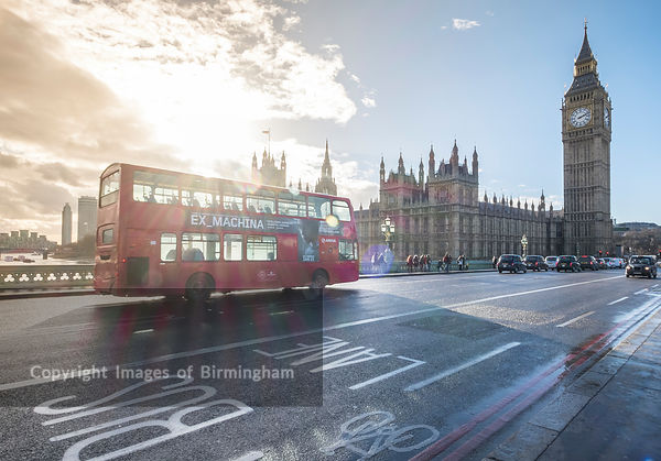 A red London bus on Westminster Bridge, in front of the Houses of Paliament, London, England