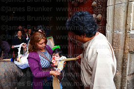Priest outside church blessing a woman and her baby with holy water after mass for Reyes (Epiphany, January 6th), La Paz, Bolivia