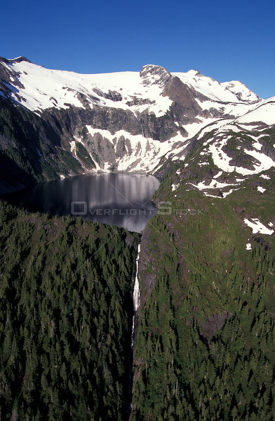 Snow-capped mountains surround fly fishing lake and waterfall near Nimmo Bay Resort, British Columbia, Canada.